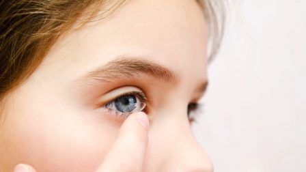 Little girl child putting contact lens into her eye closeup vision concept